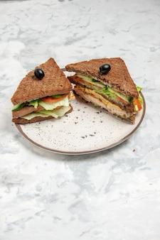 스테인드 흰색 표면에 접시에 올리브로 장식 된 검은 빵과 함께 맛있는 샌드위치의 세로보기