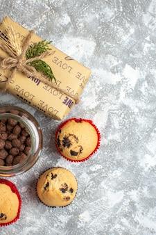 얼음 표면에 크리스마스 선물 옆에 유리 냄비에 맛있는 작은 컵 케이크와 초콜릿의 세로보기