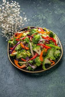 さまざまな野菜とフォークの白い花と暗い背景の空きスペースとプレートでおいしいビーガンサラダの垂直方向のビュー