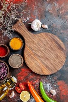 夕食の背景の垂直方向のビュー落ちたオイルボトル豆まな板とさまざまなスパイス