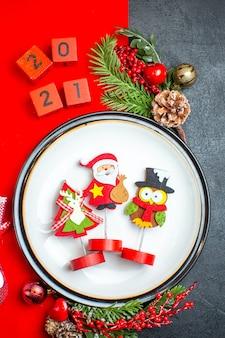 Вертикальный вид аксессуаров украшения обеденной тарелки еловые ветки и цифры рождественский носок на красной салфетке на черном столе
