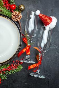 Вертикальный вид на обеденные тарелки украшения аксессуары еловые ветки рождественские носки стеклянные бокалы на темном столе