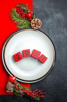 Вертикальный вид обеденных тарелок с числами и еловыми ветками с украшением из хвойных шишек на красной салфетке на темном фоне
