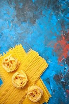 青の背景にパスタ ヌードルを使った夕食の準備の垂直方向のビュー