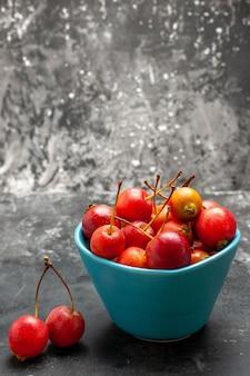 Вертикальный вид свежей вишни внутри и снаружи синей корзины на сером