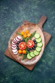 Вертикальный вид свежих нарезанных овощей в коричневой тарелке на деревянной разделочной доске на фоне смешанных цветов