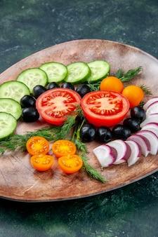 緑と黒の混合色の背景に茶色のプレートで新鮮なみじん切り野菜オリーブキンカンの垂直方向のビュー