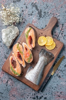 新鮮な魚の垂直方向のビューレモンスライスグリーンペッパー木製まな板とナイフブルーブラックミックスカラーテーブル