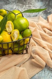 Вертикальный вид свежих кумкватов и лимонов в черной корзине на полотенце на сером фоне