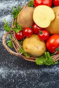 黒と白の背景の左側にある木製のバスケットに新鮮な生野菜と緑の垂直方向のビュー