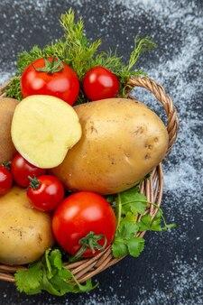 黒と白の背景の右側にある木製のバスケットに新鮮な生野菜と緑の垂直方向のビュー