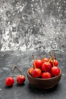 Вертикальный вид свежих красных фруктов вишни в коричневой миске на сером