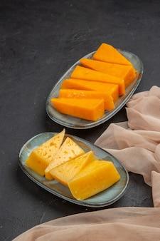 黒の背景にタオルの上の新鮮なおいしいチーズ スライスの垂直方向のビュー