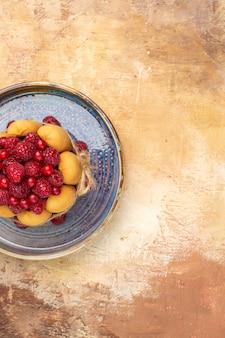 혼합 색상 배경에 과일과 함께 갓 구운 선물 케이크의 세로보기