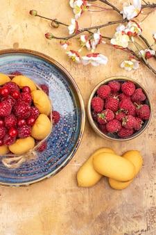 혼합 색상 테이블에 과일과 비스킷과 함께 갓 구운 부드러운 케이크의 세로보기
