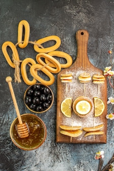 회색 테이블에 그릇에 꿀과 블랙 체리 근처 과일 팬케이크 쿠키의 세로보기