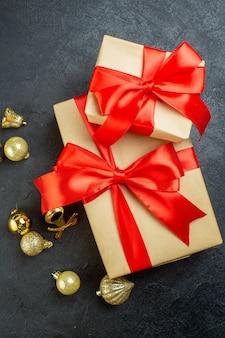 Вертикальный вид подарочной коробки с красной лентой и декоративными аксессуарами на темном фоне