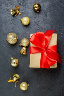 Вертикальный вид подарочной коробки с красной лентой и декоративными аксессуарами на темном столе