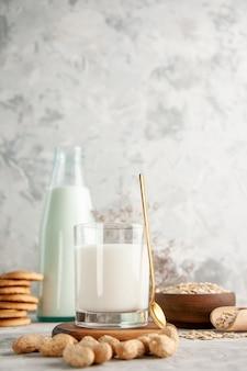 나무 쟁반에 우유로 채워진 유리병과 컵의 수직 보기와 얼음 배경에 있는 흰색 테이블의 왼쪽에 있는 갈색 냄비에 말린 과일 쌓인 쿠키 숟가락 귀리