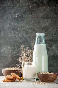 어두운 나무 배경의 회색 테이블에 있는 갈색 냄비 내부와 외부에 우유와 황금 스푼 쿠키 꽃 귀리로 채워진 유리병 컵의 수직 보기