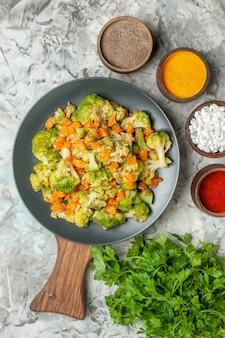 健康的な野菜サラダのさまざまなスパイスと白いテーブルの上の緑の束の垂直方向のビュー
