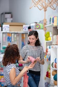 Вертикальный вид помощника-помощника в розничном магазине, помогающего женщине купить клубок розовой пряжи