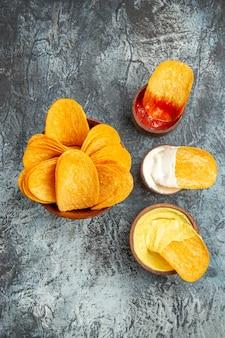 회색 배경에 만든 바삭한 감자 칩 케첩 마요네즈와 소스의 세로보기