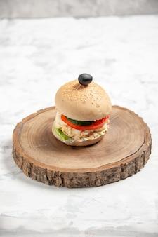 ステンドグラスの白い表面の木製まな板にブラックオリーブと自家製のおいしいサンドイッチの垂直方向のビュー