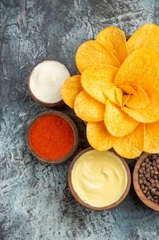 회색 배경에 마요네즈와 꽃 모양과 다른 향신료처럼 장식 된 수제 감자 칩의 세로보기