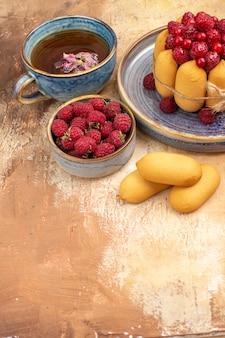 混合色のテーブルにフルーツビスケットとホットハーブティーソフトケーキの垂直方向のビュー