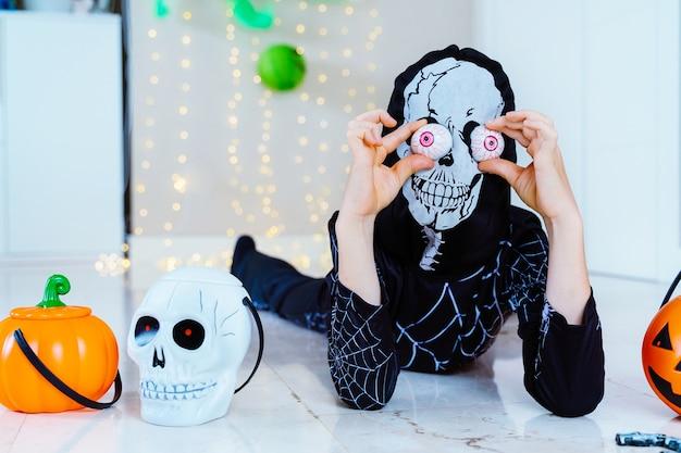 Вертикальный вид ребенка в костюме скелета-паука, делающего трюк или угощающего хэллоуин корзиной с тыквами