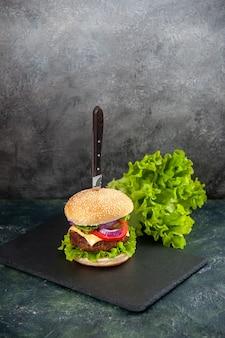 おいしい肉サンドイッチのナイフとぼやけた表面の左側の黒いトレイの緑の垂直方向のビュー