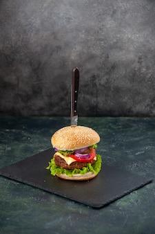 孤立したぼやけた表面上の黒いトレイにおいしいサンドイッチでナイフの垂直方向のビュー