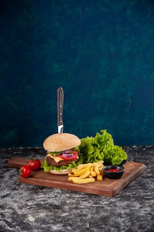 Вертикальный вид ножа в мясном бутерброде и жареных помидоров со стеблевым перцем на деревянной доске кетчупа на темно-синей поверхности