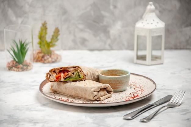 접시와 장난감 집 칼에 작은 그릇에 lavash 랩과 요구르트의 세로보기 스테인드 흰색 표면에 설정