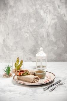 皿の上の小さなボウルとステンドグラスの白い表面にセットされたおもちゃの家のカトラリーのラヴァッシュラップとヨーグルトの垂直方向のビュー