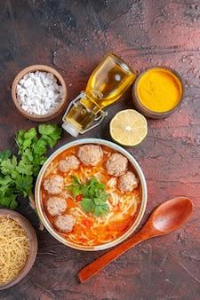 茶色のボウルに麺が入ったミートボールスープの垂直方向のビューレモンスプーン暗いテーブルに緑とオイルのボトルパスタの束