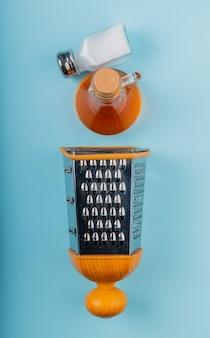 Вертикальный вид растопленного масла и соли с теркой на синем столе