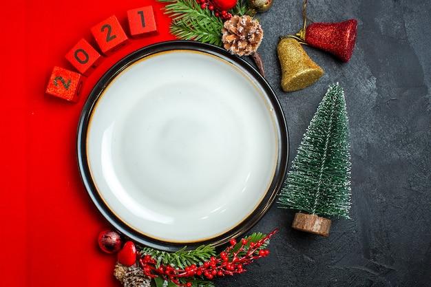Вертикальный вид новогоднего фона с аксессуарами для украшения тарелки еловые ветки и числа на красной салфетке рядом с елкой на черном столе