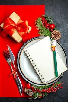 Вертикальный вид новогоднего фона со спиральной записной книжкой на обеденной тарелке, набор столовых приборов, украшения, аксессуары, еловые ветки, рядом с подарком на красной салфетке