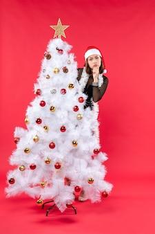 Вертикальный вид новогоднего настроения с красивой девушкой в черном платье с шапкой санта-клауса, прячущейся за елкой
