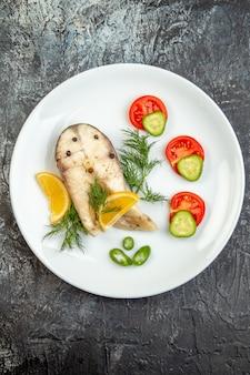 회색 얼음 표면에 흰색 접시에 원시 물고기와 고추 신선한 식품의 세로보기