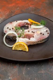 혼합 색상 표면에 검은 접시에 원시 물고기와 고추 레몬 슬라이스 양파의 세로보기 무료 사진