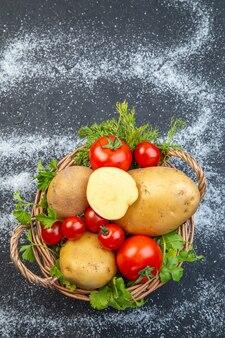 黒と白の背景に木製のバスケットに生野菜と緑の垂直方向のビュー