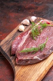 Вертикальный вид красного мяса на деревянной разделочной доске и зеленого чеснока на темном фоне
