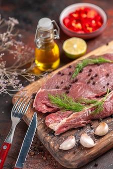 Вертикальный вид красного мяса на деревянной разделочной доске и чеснока, вилки и ножа с зеленым перцем на темном фоне