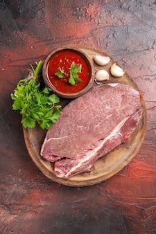 Вертикальный вид красного мяса на деревянном подносе и чесночного зеленого кетчупа на темном фоне