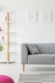 灰色のソファ、壁にヒータープリント、花瓶が付いた木製の棚、モックアップ付きの実際の写真を備えたスカンジナビアのリビングルームのデザインの垂直方向のビュー