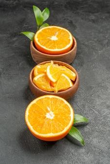 黒いテーブルの上の新鮮なレモンの葉と花の断片に半分スライスされたカットのセットの垂直方向のビュー