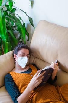 家で本を読んでフェイスマスクを着ている病気の女性の垂直方向のビュー。パンデミックウイルス病covid19。健康の概念。